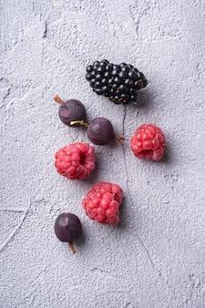 Gustoso lampone maturo fresco, mora, uva spina e ribes rosso bacche, cibo sano frutta sulla pietra tavolo in cemento, vista dall'alto macro