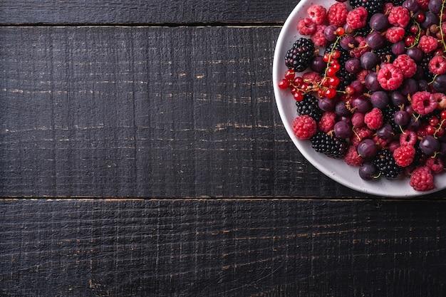 Bacche mature fresche saporite del lampone, della mora, dell'uva spina e del ribes in piatto
