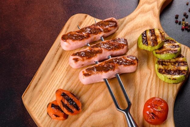 Gustose salsicce fresche alla griglia con verdure, spezie ed erbe aromatiche. foto del piatto finito su un tavolo di cemento scuro