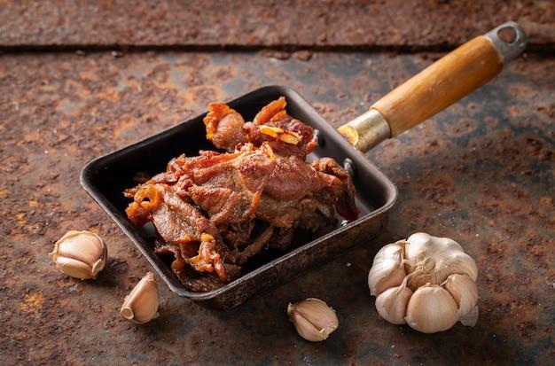 Filetto di maiale fritto saporito con aglio in una vecchia padella su fondo arrugginito di struttura
