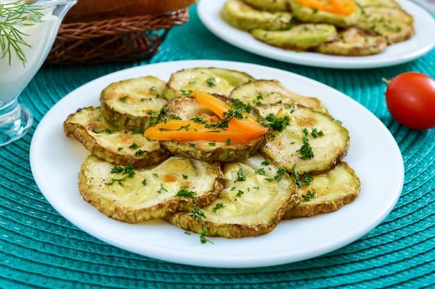 Gustose fette di zucchine fritte su un piatto con salsa su un tavolo di legno. merenda picnic. stile rustico