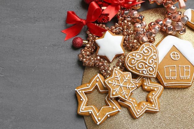 Gustosi biscotti di pan di zenzero e decorazioni natalizie su sfondo grigio