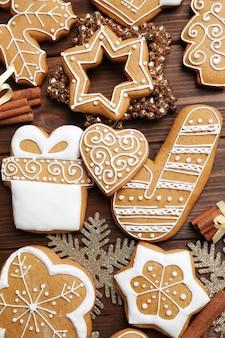 Gustosi biscotti di pan di zenzero e decorazioni natalizie su una superficie di legno, primo piano
