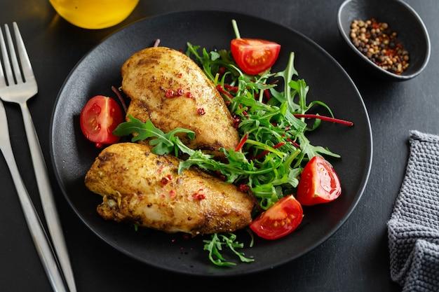 Gustoso petto di pollo alla griglia con verdure e insalata servita su un tavolo scuro.