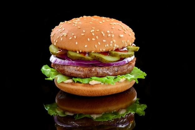 Gustosi hamburger fatti in casa alla griglia con carne di manzo. su uno sfondo nero