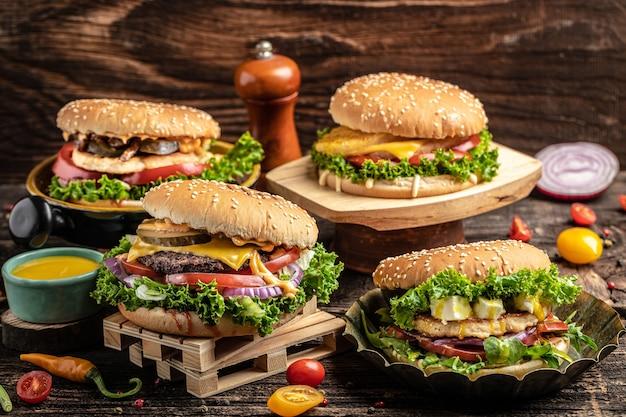 Gustosi hamburger fatti in casa alla griglia con manzo, pomodoro, formaggio, pancetta e lattuga su fondo di legno rustico. fast food e concetto di cibo spazzatura