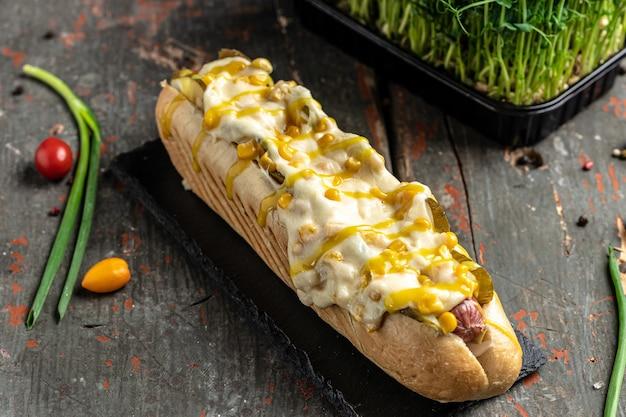 Gustoso hot dog alla griglia fatto in casa con salsiccia, formaggio e mais. banner, menu, posto ricetta per testo, vista dall'alto.
