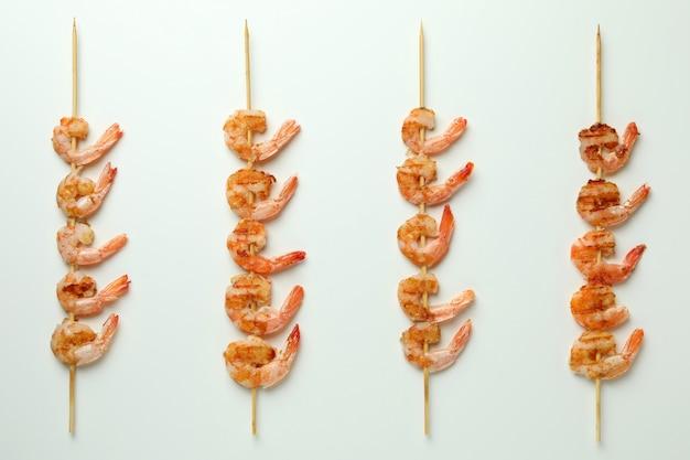 Spiedini di gamberi alla griglia gustosi su sfondo bianco