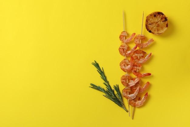 Spiedini di gamberi alla griglia gustosi su sfondo giallo