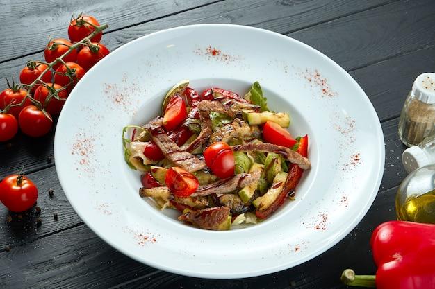 Insalata calda saporita e sana con arrosto di manzo e verdure grigliate con olio d'oliva in un piatto bianco su una superficie di legno nera