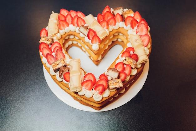 Gustosa torta a forma di cuore con frutti di bosco freschi su sfondo nero.