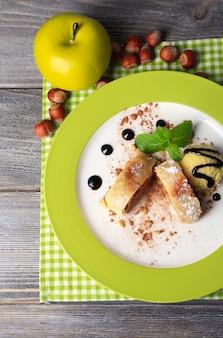 Gustoso strudel di mele fatto in casa con noci, foglie di menta e gelato su piatto, su fondo di legno