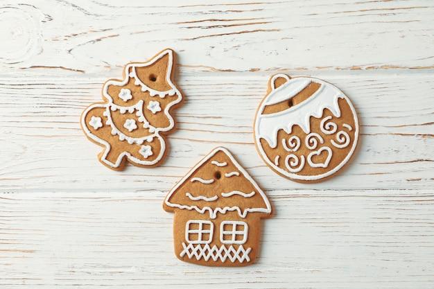 Biscotti casalinghi saporiti di natale su di legno bianco, spazio per testo. vista dall'alto