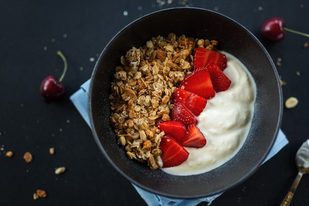 Gustosa muesli fruttata fatta in casa servita in una ciotola con yogurt su sfondo scuro. avvicinamento