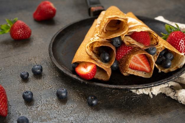 Gustoso pancake rustico fatto in casa con frutti di bosco in una padella sul tavolo di legno. il cibo di maslenitsa.