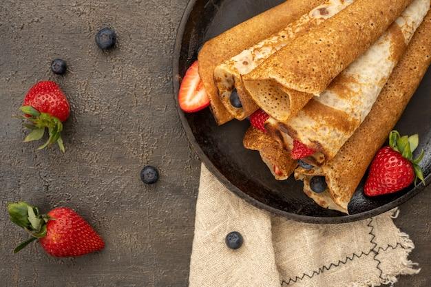 Gustoso pancake rustico fatto in casa con frutti di bosco in una padella sul tavolo di legno. vista dall'alto del tavolo. il cibo di maslenitsa.