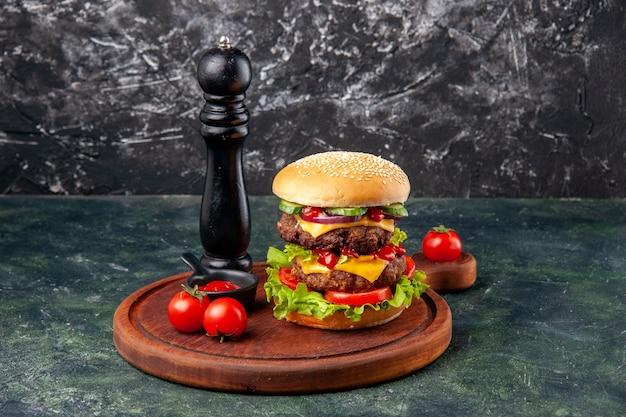 Gustoso panino fatto in casa pomodori pepe sul tagliere di legno sulla superficie di colore scuro