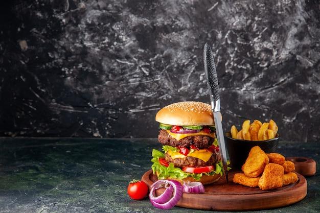 Gustoso panino fatto in casa pomodori pepe sul tagliere di legno cipolle pomodoro con gambo pepite di pollo patatine fritte sul lato sinistro sulla superficie di colore scuro