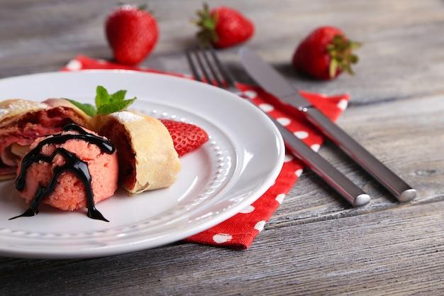 Gustoso strudel fatto in casa con gelato, fragole fresche e foglie di menta su piatto, su superficie di legno
