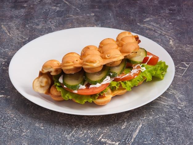 Gustosi waffle di hong kong con verdure fresche su un piatto bianco