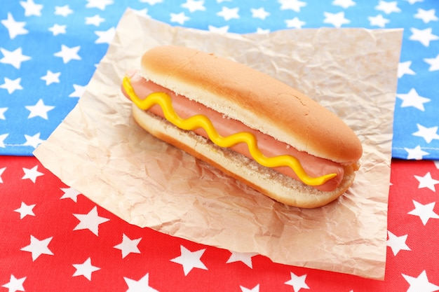 Gustoso hot dog sul tovagliolo con stelle, isolato su bianco
