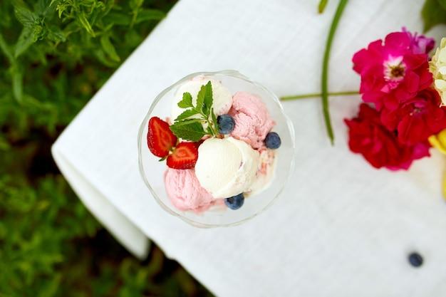 Gustoso gelato e mirtilli freschi, fragole nella ciotola, presentati con fiori su un tavolo in un giardino durante la stagione estiva per una festa