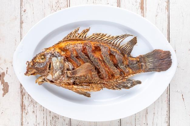 Gustoso grande pesce tilapia fritto del nilo in piatto ceramico bianco su fondo di legno vecchio bianco di struttura, vista dall'alto