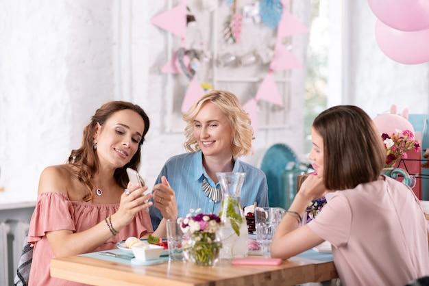 Gustoso pranzo. tre donne alla moda di successo che indossano graziosi accessori si sentono sollevate mentre mangiano un gustoso pranzo