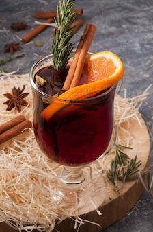 Gustoso vin brulè con vino cannella arancia su un supporto in legno