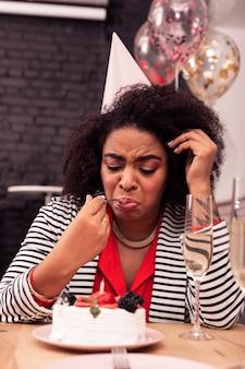 Non gustoso. bella donna triste che si sente sconvolta mentre prova la sua torta di compleanno