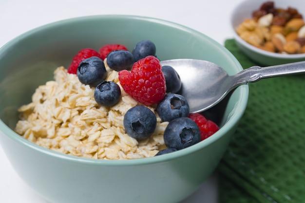 Gustosa farina d'avena con frutti di bosco sul tavolo bianco.
