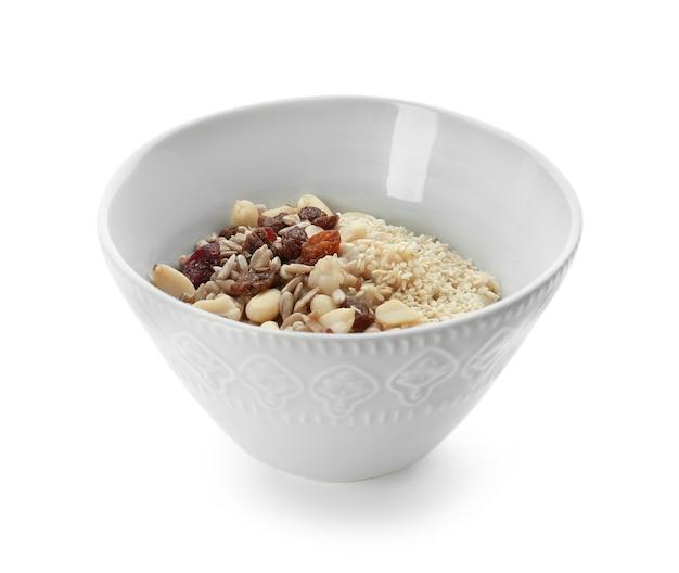 Gustosa farina d'avena con noci e uvetta in una ciotola su bianco
