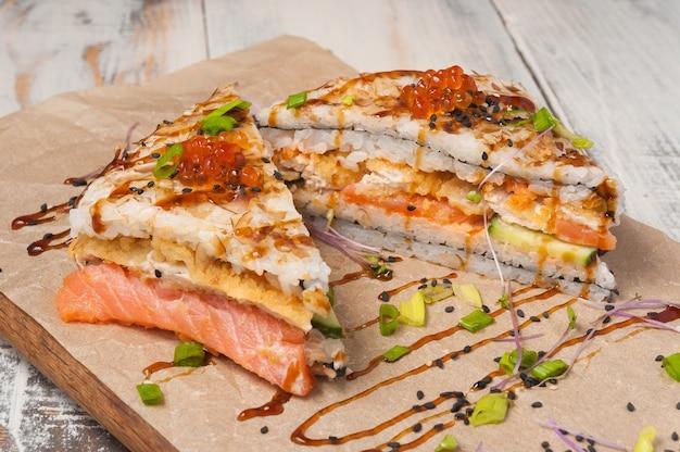 Gustoso sushi onigirazu con salmone fritto in profondità, pesce bianco, cetriolo, caviale rosso e chips di tonno