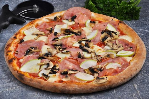 Gustosa pizza di parma con funghi zucchine prosciutto su uno sfondo grigio