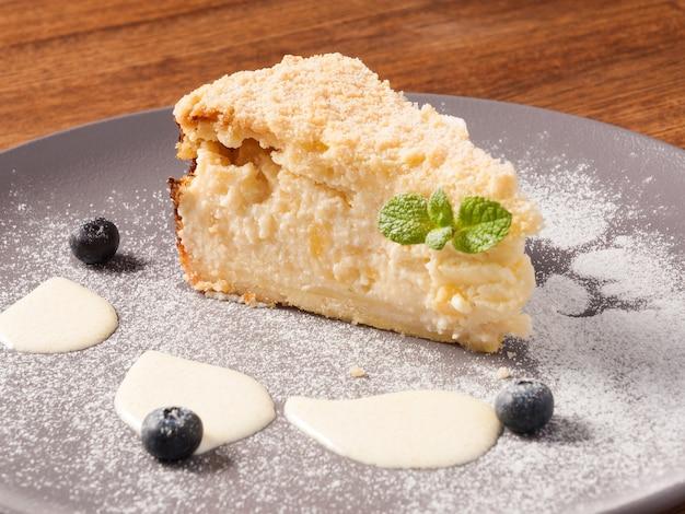 Torta tedesca gustosa pera su un piatto decorato con frutti di bosco