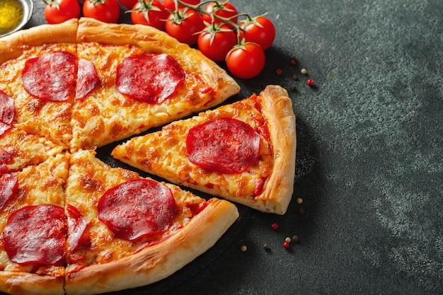 Gustosa pizza ai peperoni e ingredienti da cucina.