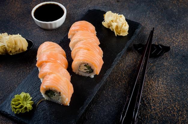 Gustoso sushi roll philadelphia con salmone e crema di formaggio su lastra di pietra nera con salsa di soia
