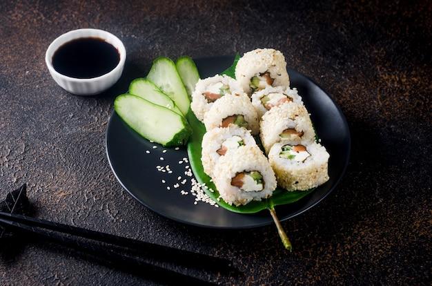 Gustoso rotolo di sushi di filadelfia con salmone e crema di formaggio al sesamo su banda nera con salsa di soia, zenzero, wasabi e bacchette sul tavolo scuro. menù sushi. servizio di consegna cibo asiatico giapponese.