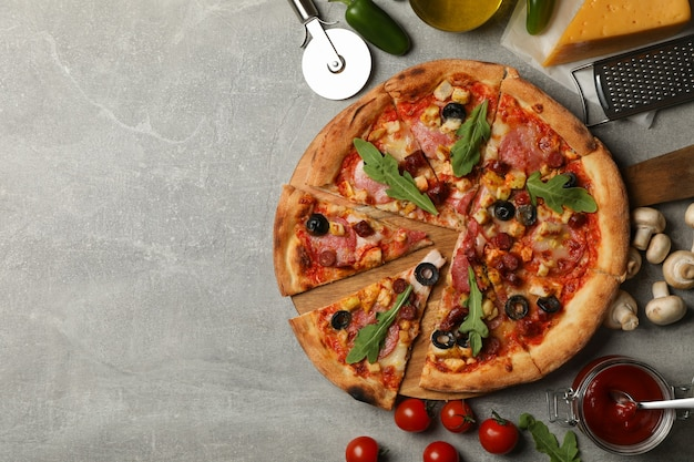 Gustosa pizza e ingredienti su grigio