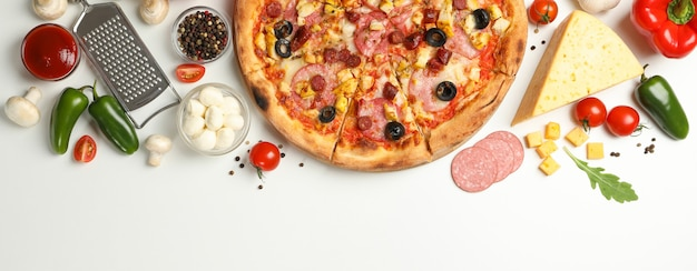 Pizza ed ingredienti saporiti su bianco