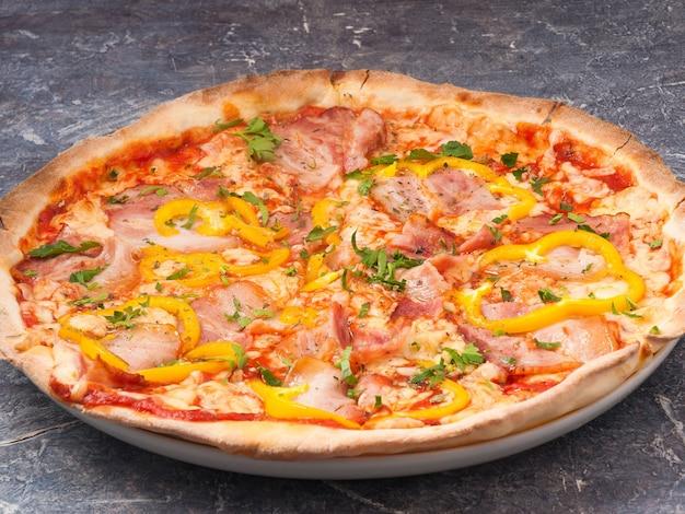 Gustosa pizza con pancetta e peperone, salsa di pomodoro, decorata con verdure