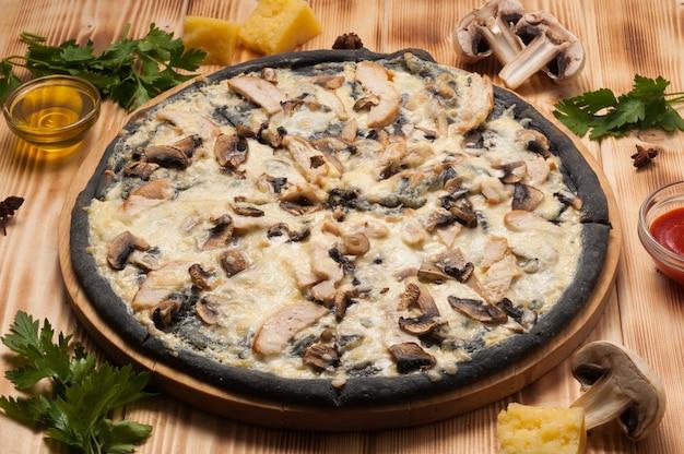 Gustosa pizza con pollo e funghi su pasta nera