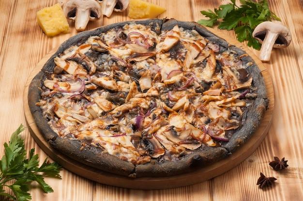 Gustosa pizza con pollo e funghi e salsa teriyaki su pasta nera