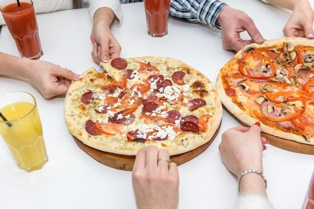 Pizza gustosa con mani umane sul tavolo da vicino