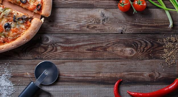 Pizza gustosa con ingredienti su una tavola di legno. vista dall'alto con spazio vuoto al centro