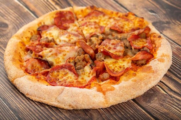Gustosa pizza con carne mista posta sul tavolo di legno.