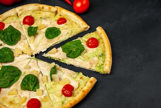 Gustosa pizza con ananas, pomodori, mozzarella, filetto di pollo su uno sfondo di pietra con copia spazio per il testo