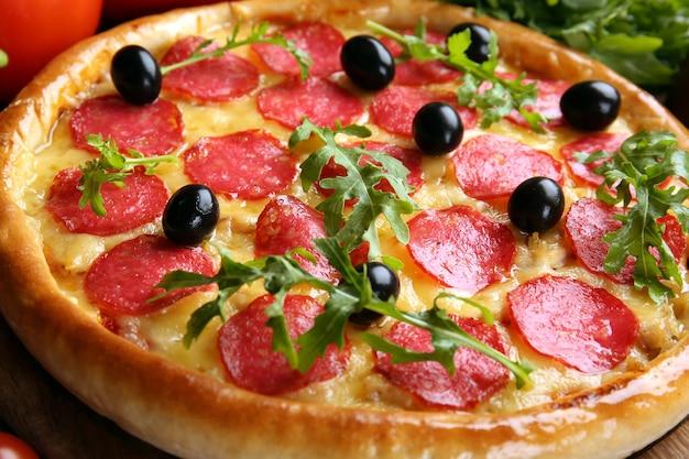 Gustosa pizza con salame sulla tavola di legno decorata