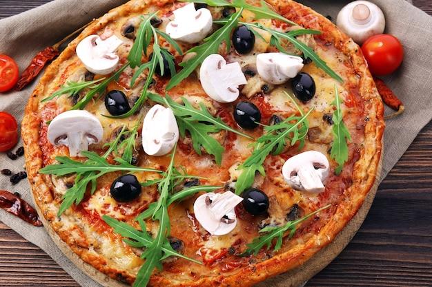 Gustosa pizza con verdure e rucola sul tavolo da vicino