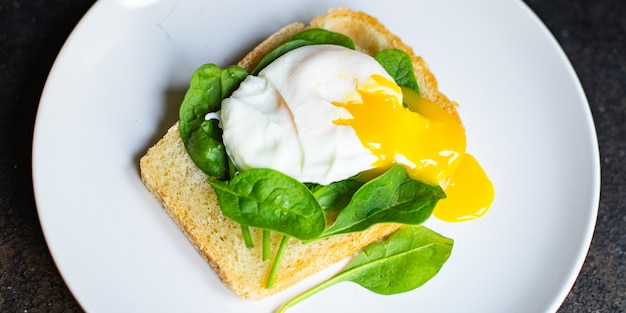 Gustosi spinaci panino uovo in camicia sul tavolo